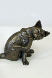 bronze resin Cat sitting licking one paw