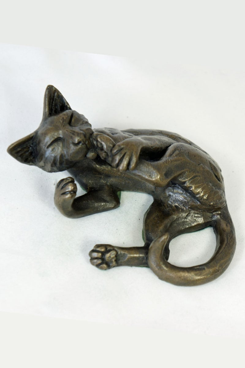 bronze resin Cat lying licking its foot