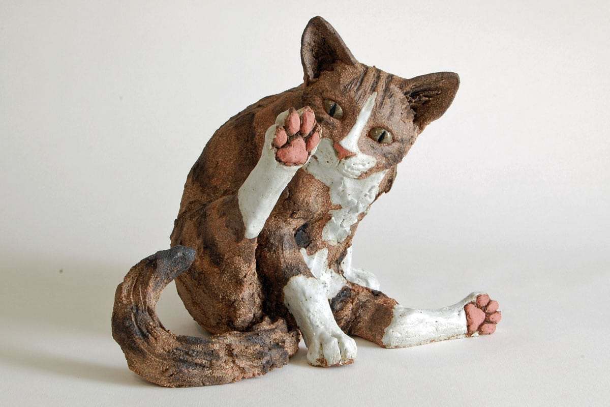Tabby Cat, Contemplating his back leg - ceramic clay sculpture